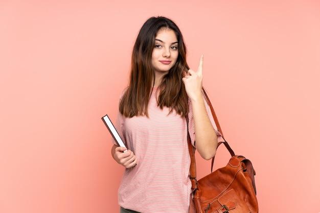 Mujer joven estudiante que va a la universidad sobre pared rosa aislado con expresión facial sorpresa