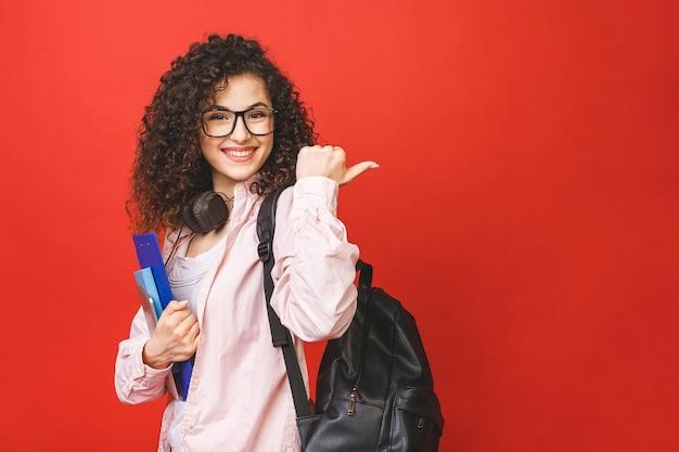 Mujer joven estudiante rizado con mochila