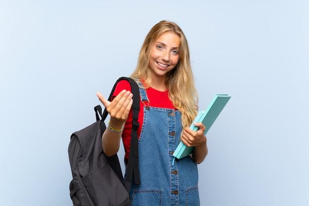 Mujer joven estudiante rubia sobre pared azul aislada invitando a venir