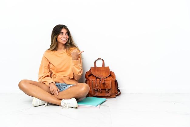Mujer joven estudiante sentada en el suelo con un portátil aislado sobre fondo blanco apuntando hacia el lado para presentar un producto