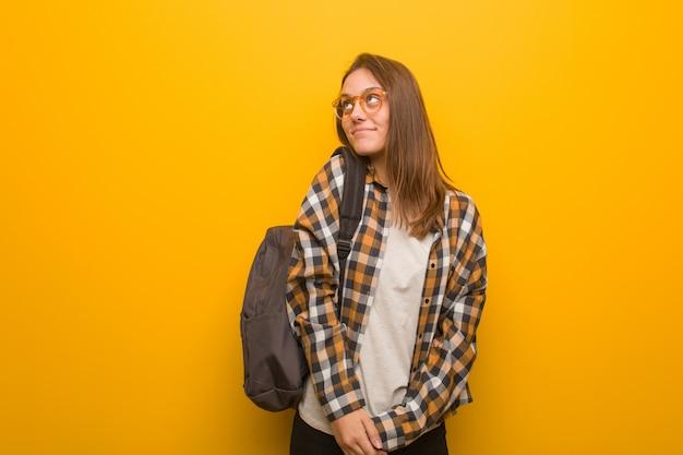 Mujer joven estudiante soñando con alcanzar objetivos y propósitos