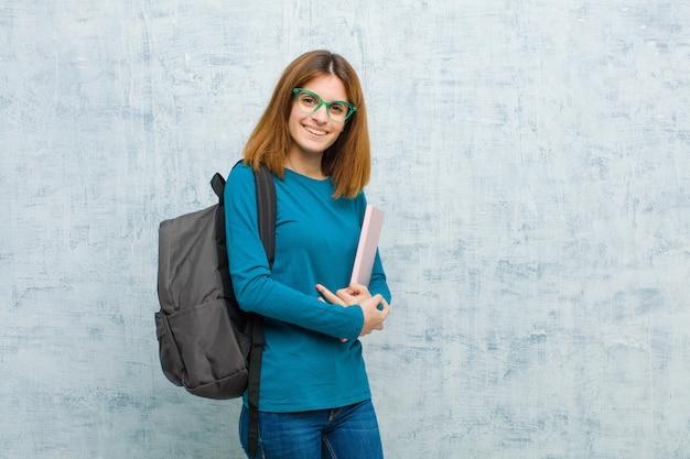 Mujer joven estudiante sonriendo a la cámara con los brazos cruzados y una expresión feliz, segura y satisfecha, vista lateral en la pared del grunge