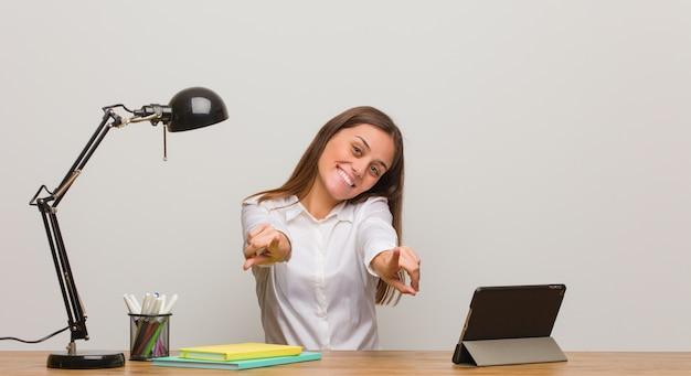 Mujer joven estudiante trabajando en su escritorio alegre y sonriente apuntando al frente