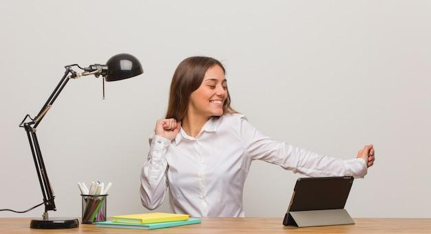 Mujer joven estudiante trabajando en su escritorio bailando y divirtiéndose