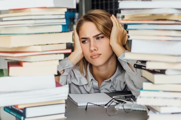 Mujer joven estudiante universitaria infeliz en una biblioteca, posando con gafas y libros.