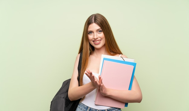 Mujer joven estudiante en verde aplaudiendo