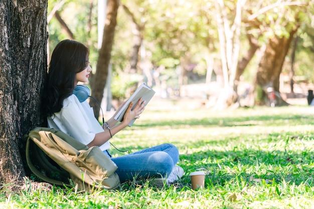 La mujer joven de los estudiantes se relaja y leyendo un libro que se sienta en hierba en parque