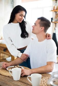 Mujer joven étnica abrazando novio sentado junto a la mesa