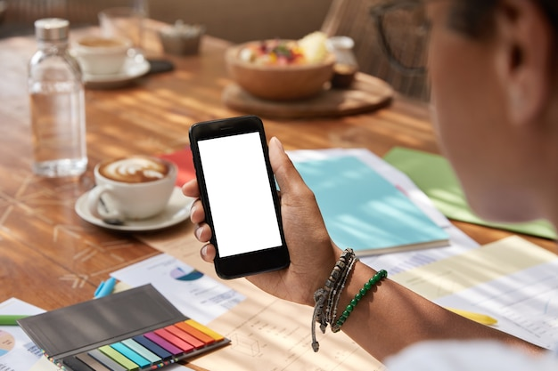 Mujer joven étnica irreconocible sostiene moderno teléfono inteligente con pantalla en blanco