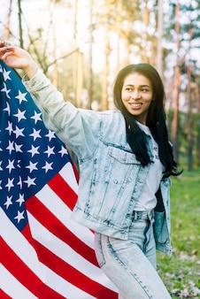 Mujer joven étnica ondeando la bandera de estados unidos