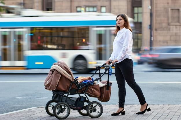 Mujer joven europea con bebé en cochecito está caminando en la calle cerca del tráfico.