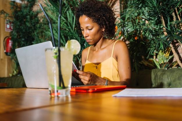 Mujer joven examinando el documento en el restaurante