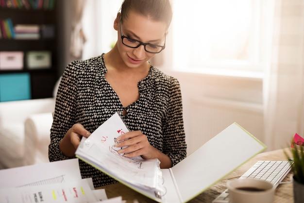 Mujer joven examinando documentos en la carpeta de anillas