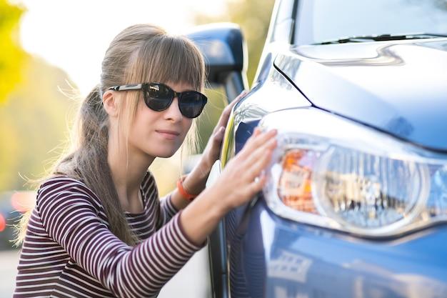 Mujer joven examinar coche nuevo en la tienda de ventas del concesionario antes de la compra.