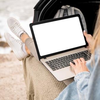 Mujer joven, examinar, computadora portátil, en, viaje por carretera