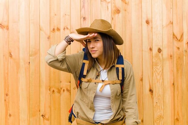 Mujer joven explorador latino en pared de madera