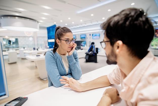 Mujer joven con expresión de la cara seria con la mano en la barbilla escuchando al cajero
