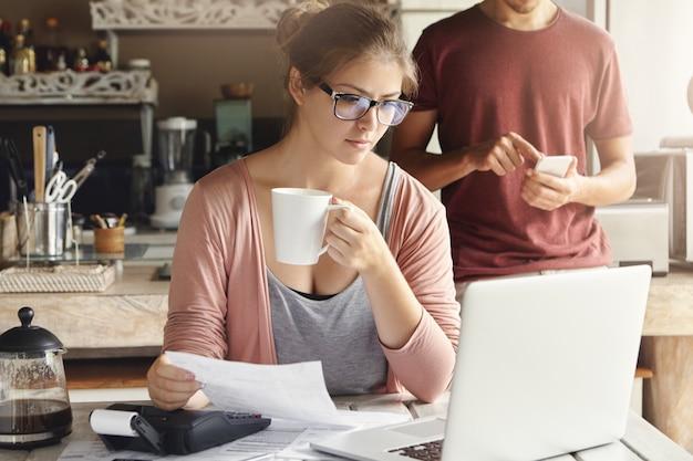 Mujer joven con expresión concentrada mirando la pantalla de la computadora portátil abierta, sosteniendo papel y una taza de café en sus manos mientras calcula los gastos domésticos