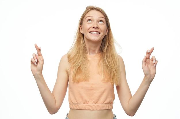 Mujer joven, con expresión facial feliz, viste camiseta naranja y pantalones de mezclilla azul, reza con los dedos cruzados para obtener un examen médico negativo