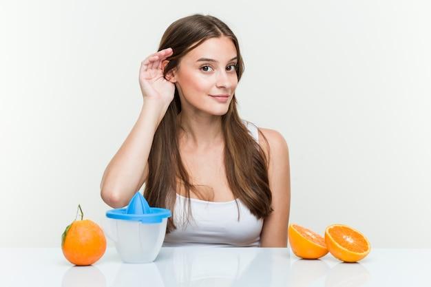 Mujer joven con un exprimidor de naranja tratando de escuchar un chisme