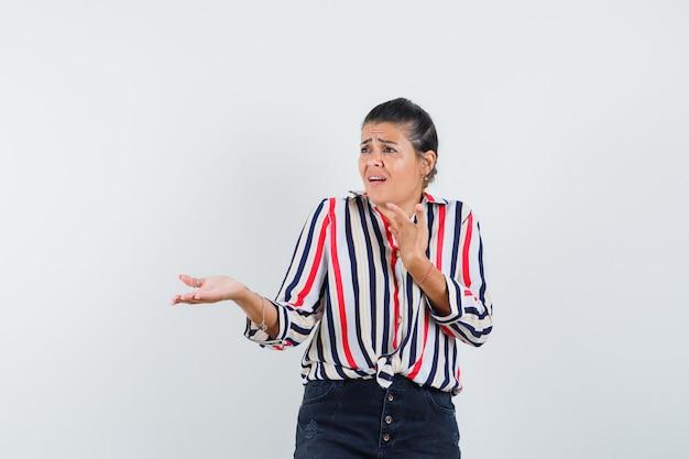 Mujer joven extendiendo la palma como recibiendo algo en blusa rayada y mirando sorprendido.