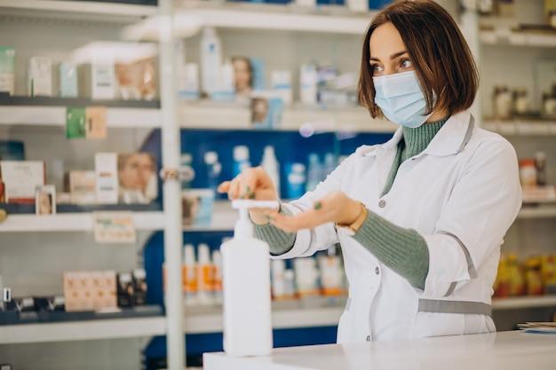 Mujer joven farmacéutico desinfectar las manos con sanitazer