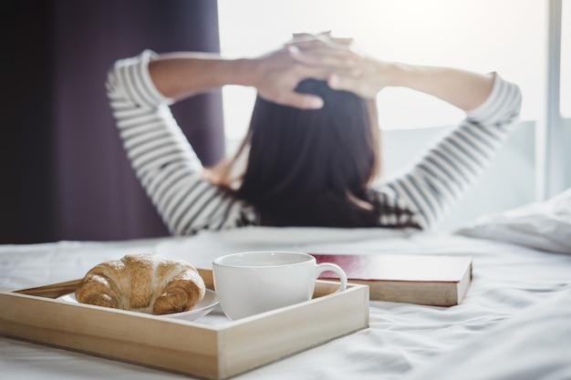 Mujer joven felicidad en la cama con el viejo libro