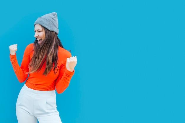 Mujer joven feliz acertada con los puños de apretón delante de la superficie azul