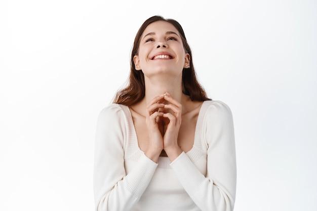 Mujer joven feliz agradeciendo a dios, luciendo aliviada y alegre en la parte superior, diciendo oración, expresando gratitud y deleite, pidiendo deseos, regocijándose mientras está de pie contra la pared blanca