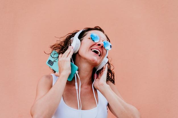 Mujer joven feliz al aire libre escuchando música en auriculares y teléfono móvil. estilo de vida en la ciudad. hora de verano. vista de cerca