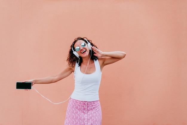 Mujer joven feliz al aire libre escuchando música en auriculares y teléfono móvil. estilo de vida en la ciudad. hora de verano