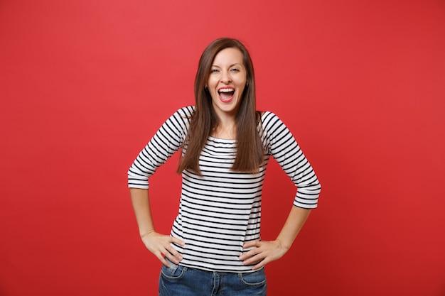 Mujer joven feliz alegre en ropa de rayas manteniendo la boca abierta, de pie con los brazos en jarras