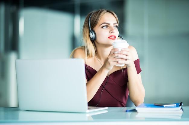 Mujer joven feliz en auriculares en call center y tomando café en la oficina.