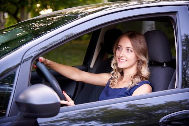 Mujer joven feliz en un auto negro.