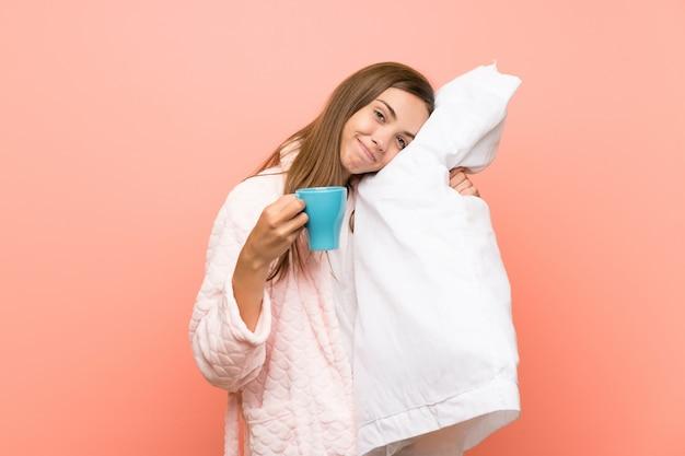 Mujer joven feliz en la bata sobre la pared rosada que sostiene una taza de café