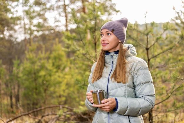 Mujer joven feliz bebiendo té y disfrutando en el bosque de otoño.