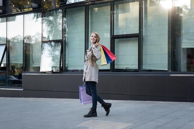 Mujer joven feliz con bolsas de colores cerca de centro comercial.
