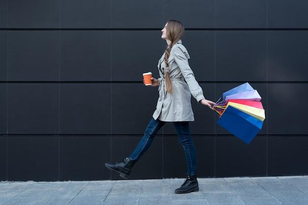 Mujer joven feliz con bolsas de colores y taza de papel caminando en la calle.