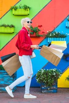 La mujer joven feliz con los bolsos acerca a la pared