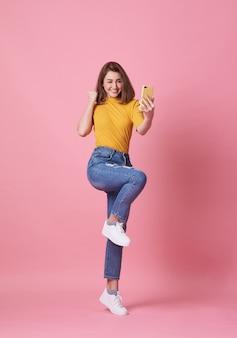 Mujer joven feliz celebrando con teléfono móvil aislado en rosa.