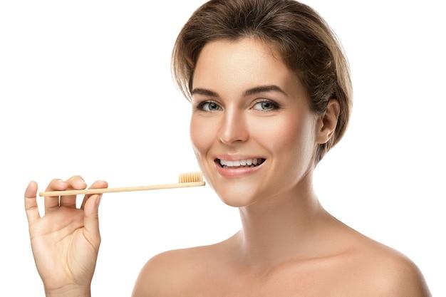 Mujer joven feliz con cepillo de dientes de bambú ecológico