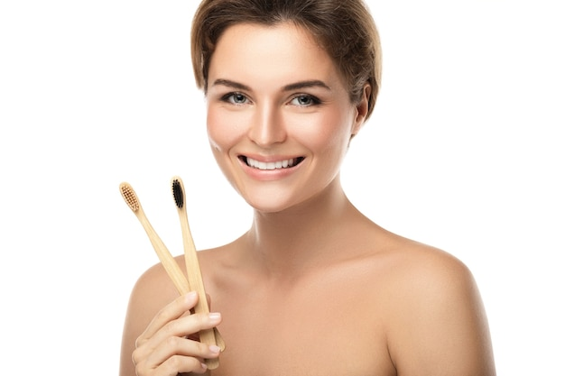 Mujer joven feliz con cepillos de dientes de bambú ecológicos