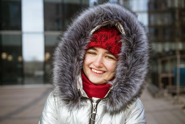 Mujer joven feliz con una chaqueta y un sombrero rojo, con una mochila viaja por las ciudades