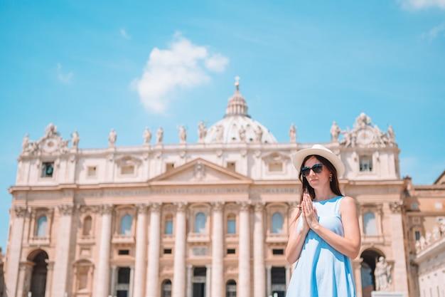 Mujer joven feliz en la ciudad del vaticano y la iglesia de la basílica de san pedro, roma, italia.