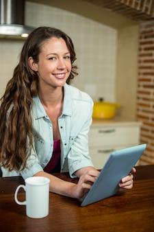 Mujer joven feliz en cocina usando la tableta digital y la taza de café en worktop