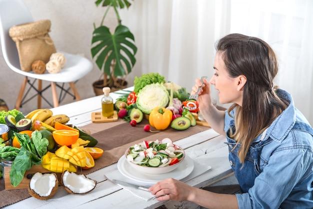 Mujer joven y feliz comiendo ensalada en la mesa