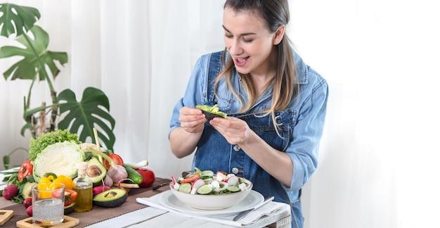 Mujer joven y feliz comiendo ensalada con verduras orgánicas en la mesa sobre un fondo claro, con ropa de mezclilla. el concepto de comida casera saludable.