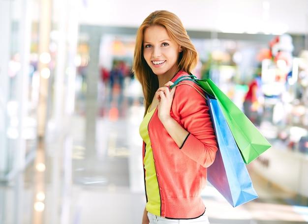 Mujer joven feliz comprando