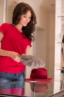 Mujer joven feliz de compras en la tienda de boutique - de pie cerca de glasscase y elegir el sombrero