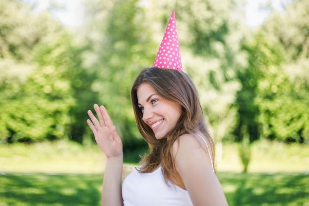 Mujer joven feliz en cono de vacaciones sonriendo, bailando y celebrando su cumpleaños solo
